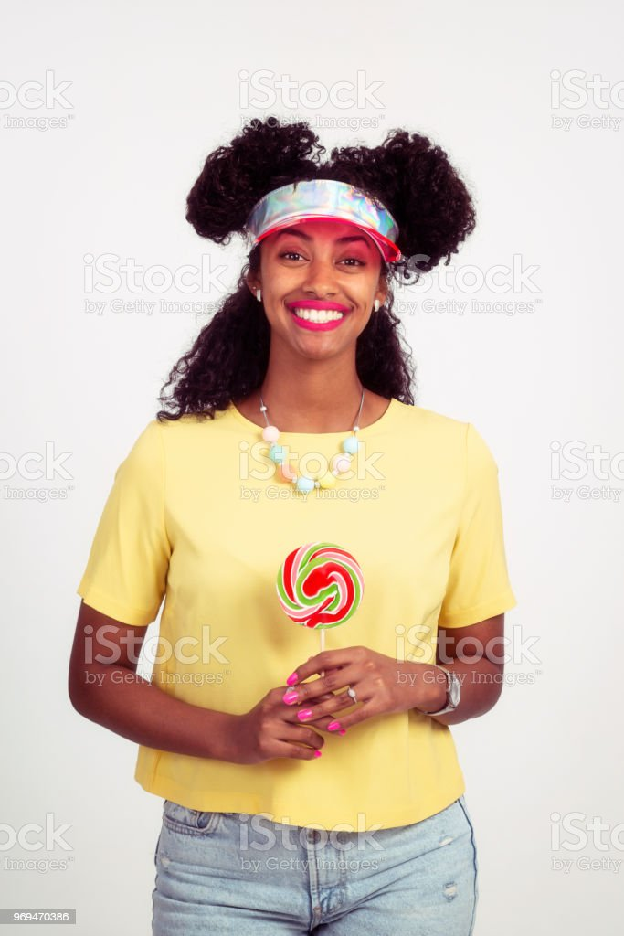 A happy woman holding colorful sweet swirl wheel lollipop. stock photo