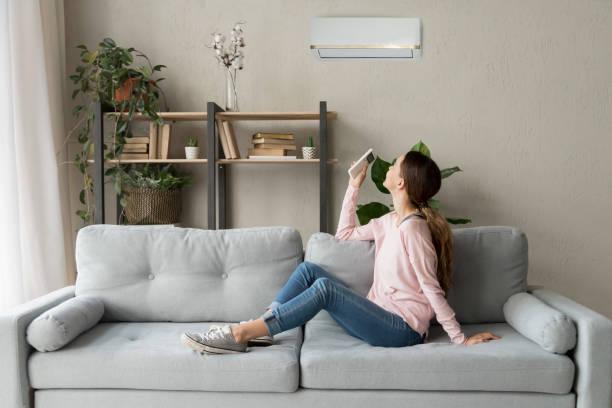 lycklig kvinna som håller svalare system fjärrkontroll njuta av frisk luft - kvinna ventilationssystem bildbanksfoton och bilder