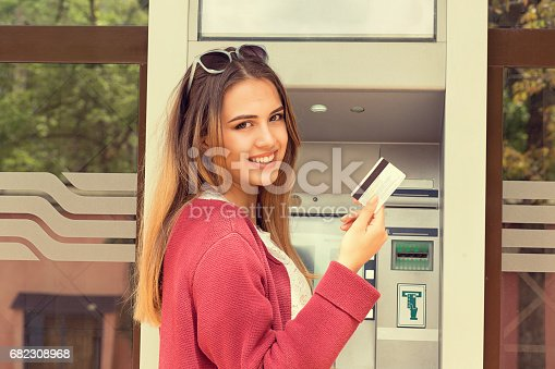 istock Happy Woman Holding Credit Card near ATM 682308968