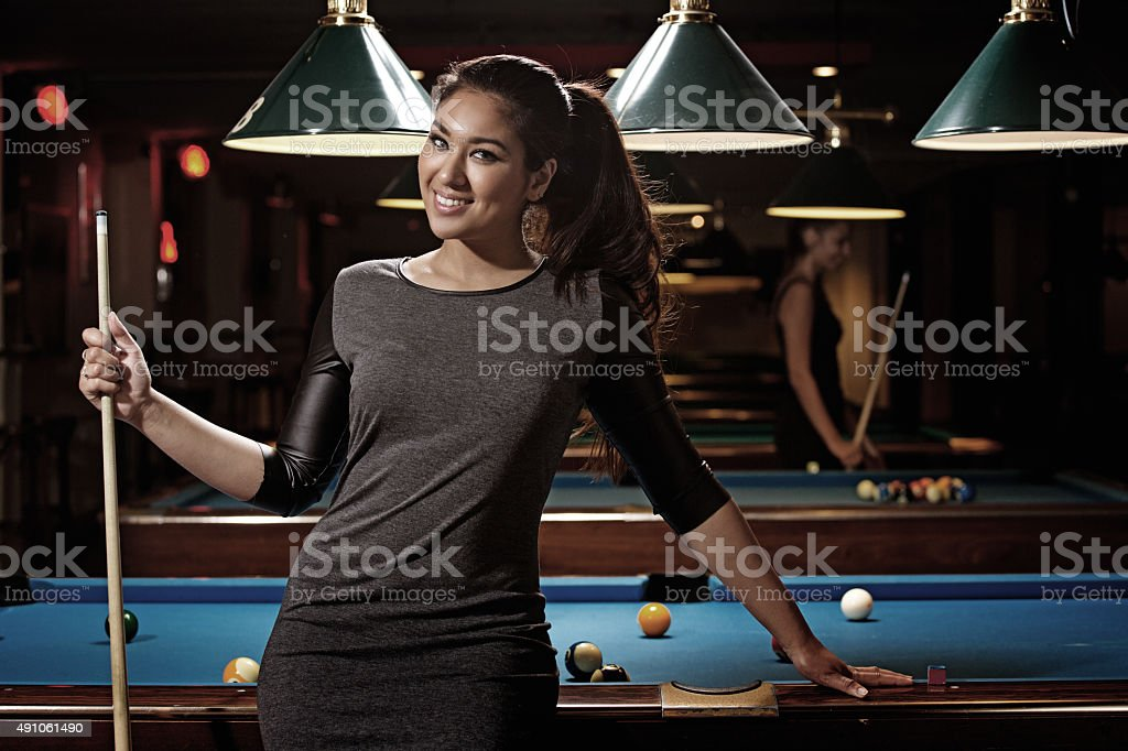 happy woman holding cue posing at pool hall