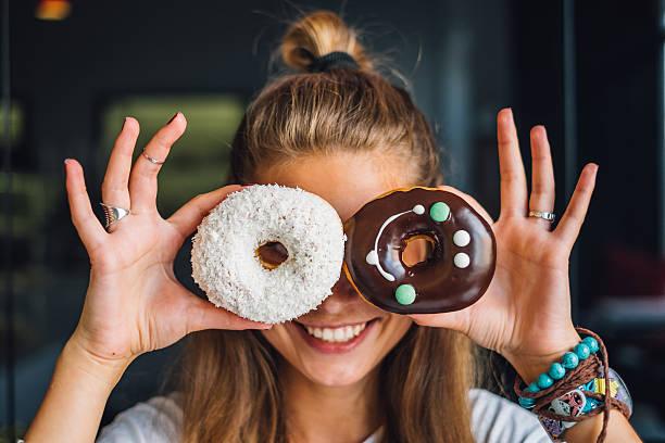 happy woman holding donuts - comida doce - fotografias e filmes do acervo