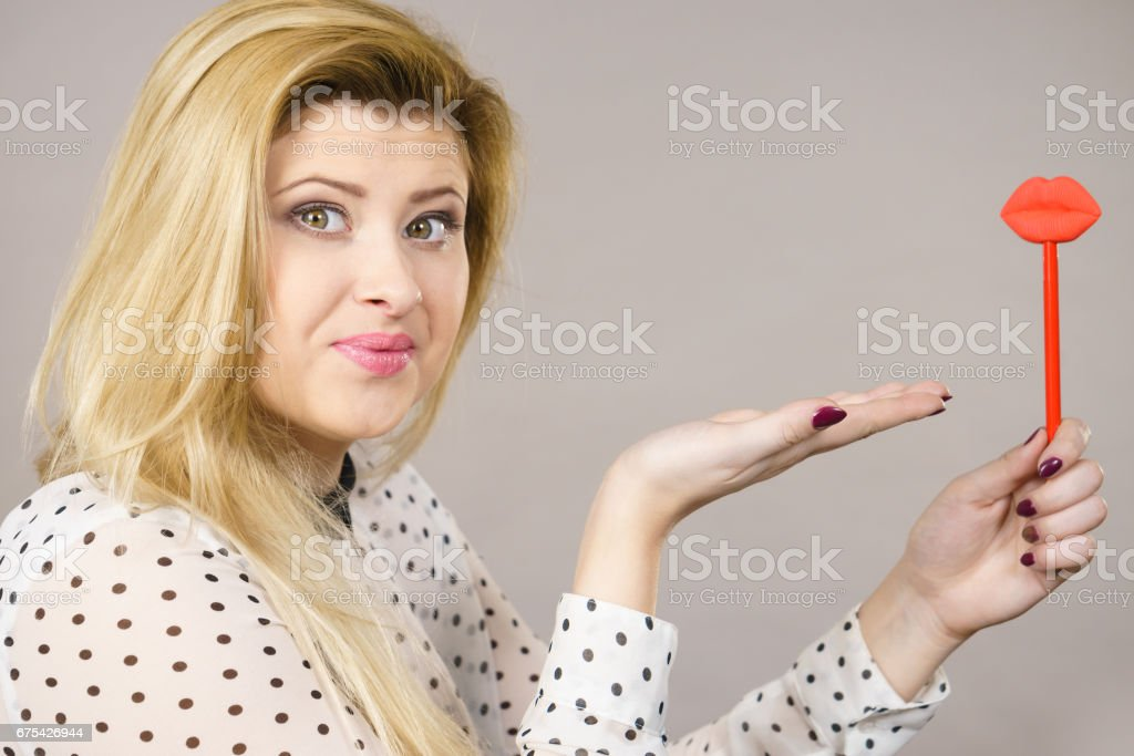 Happy woman holding fake lips on stick royalty-free stock photo