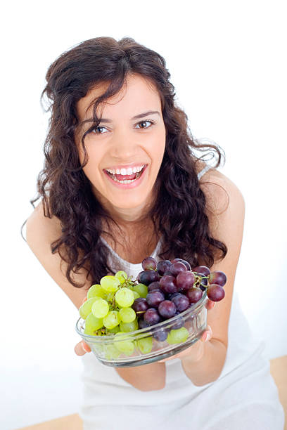 happy woman holding fresh grapes stock photo