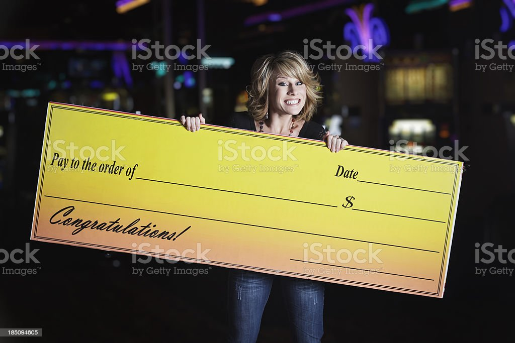 Happy Woman Holding Giant Check In a Casino stock photo
