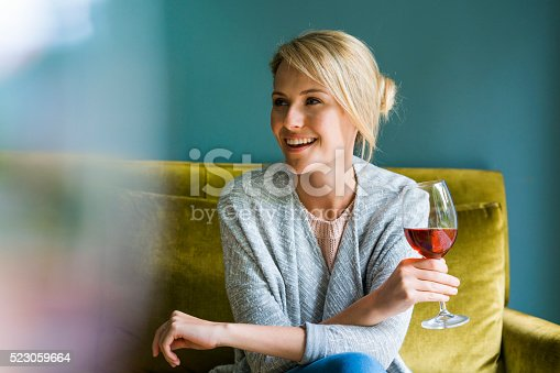 A photo of beautiful woman holding glass of red wine. Young female is looking away while sitting on sofa. Happy and relaxed lady is at home.
