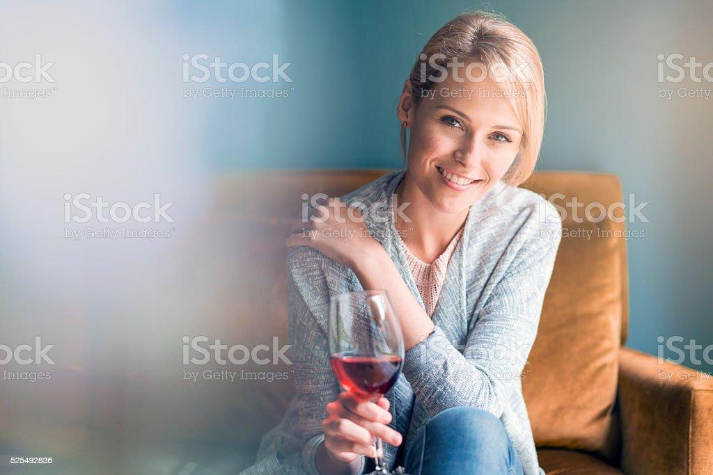 Heureuse femme tenant verre de vin rouge sur un canapé - Photo
