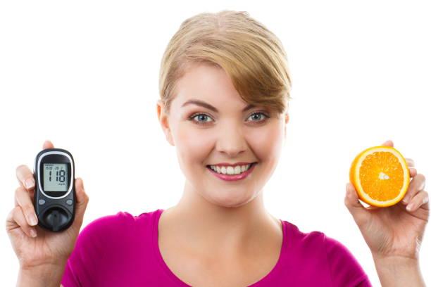 Glückliche Frau hält Glukometer und frische Orange, Messung und Kontrolle Zuckerspiegel, Konzept von Diabetes – Foto
