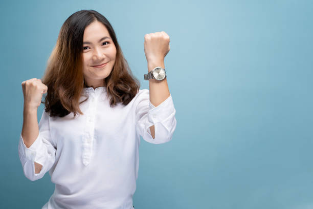 Happy woman holding hand with wrist watch isolated on a blue background stock photo