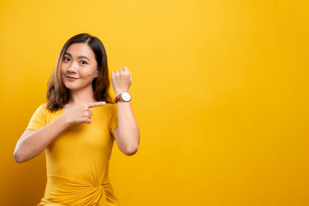 Happy woman holding hand with wrist watch isolated on a yellow background stock photo