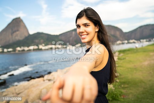 Happy woman holding hands and looking at camera in Rio de Janeiro