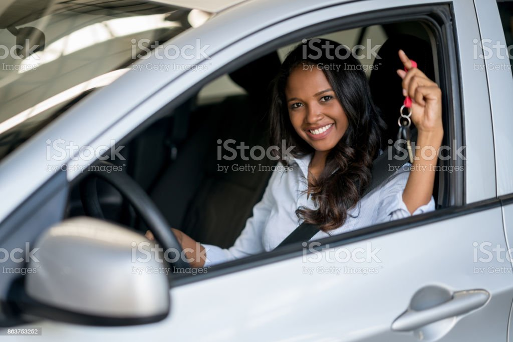 Happy woman holding keys of a car at the dealership stock photo