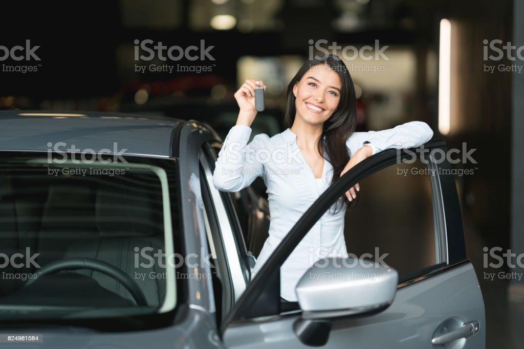 Femme heureuse possession des clefs de sa voiture neuve chez le concessionnaire - Photo