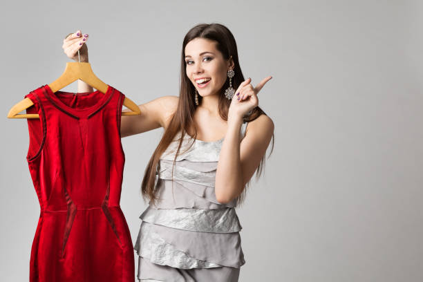 Happy Woman Holding Red Dress on Hanger, Fashion Model Clothes and Pointing on White stock photo