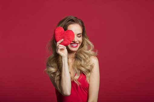Portrait of beautiful long blond hair woman wearing red dress covering eye with red heart. Studio shot against red background. Valentine's day concept.