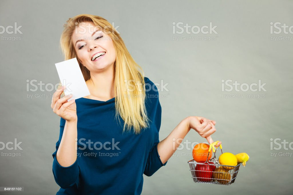 Happy woman holding shopping basket with fruits stock photo