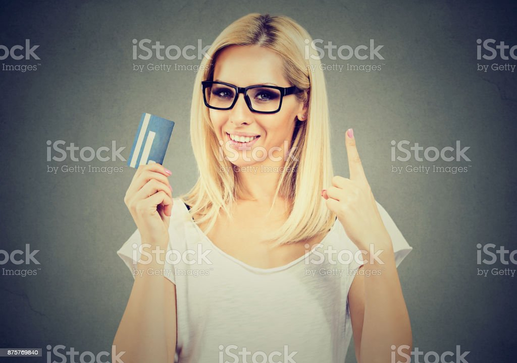 Happy woman holding showing number one credit card stock photo
