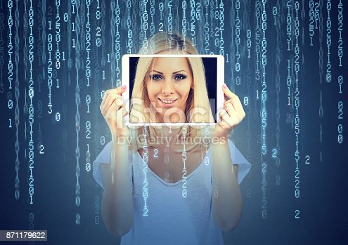 istock Happy woman holding tablet with her face displayed on a screen isolated on binary code background 871179622