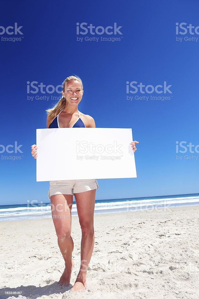 Full frame woman holding a sign on the beach
