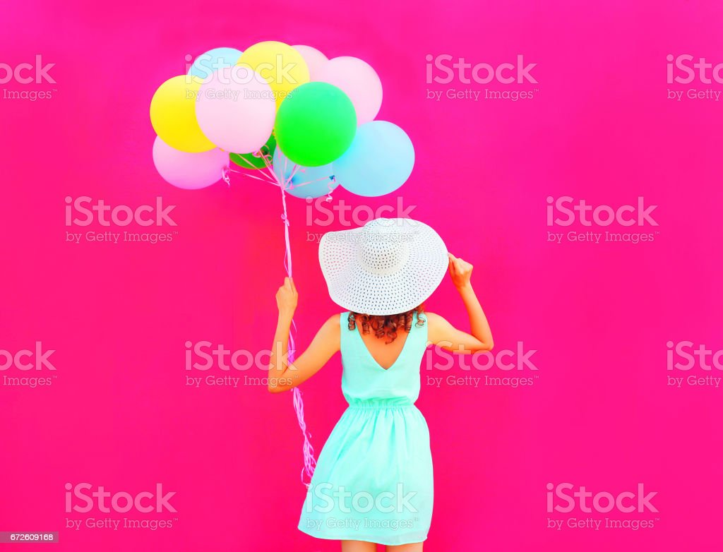 Happy woman holds an air colorful balloons is having fun on a pink background stock photo