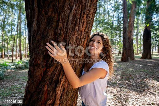 Portrait of a very happy woman hugging a tree at the park and enjoying nature