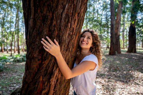 Glückliche Frau umarmt einen Baum im Park – Foto