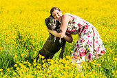 Happy woman hugging her dog in a meadow