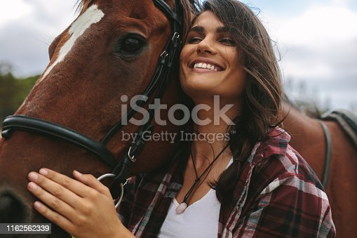 Close up of happy young woman hugging her horse. Cowgirl loving her horse outdoors.