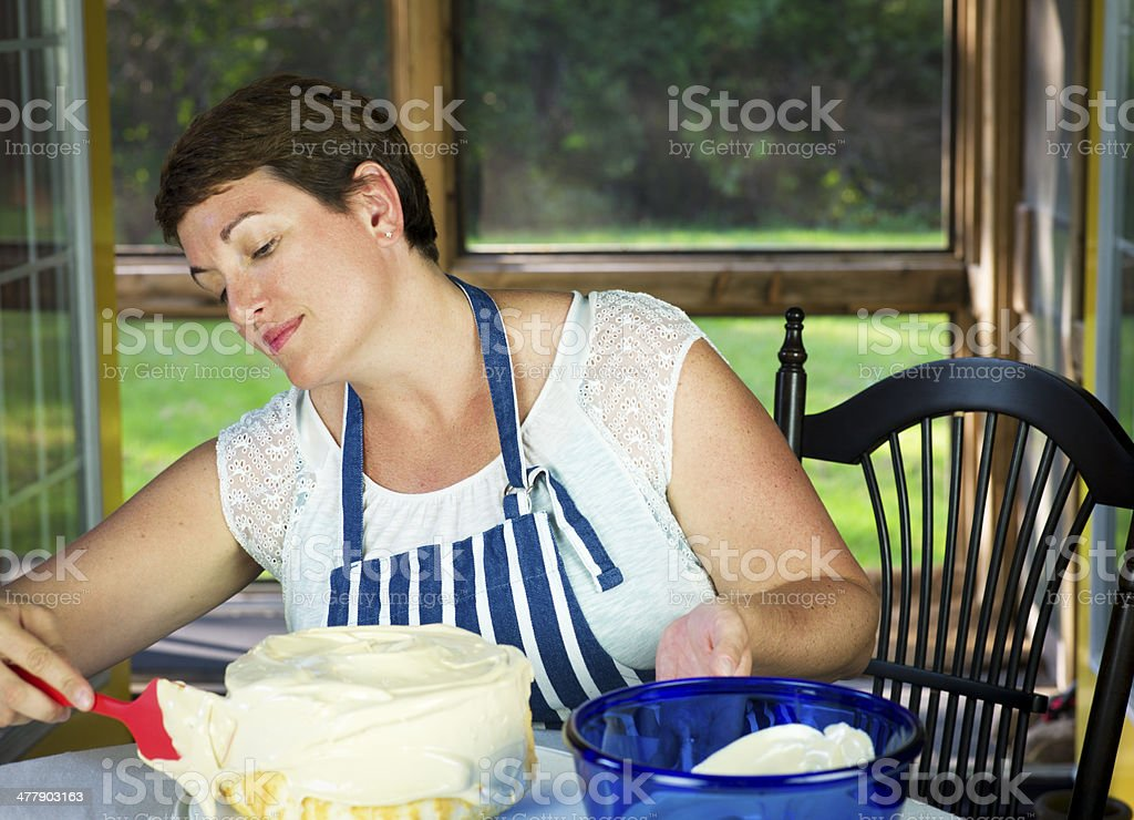 Happy Woman Icing a Cake royalty-free stock photo