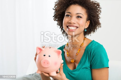 istock A happy woman in a turquoise shirt holding a piggy bank 164520839