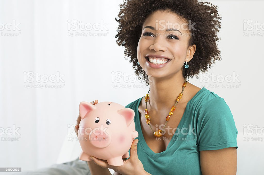 A happy woman in a turquoise shirt holding a piggy bank stock photo