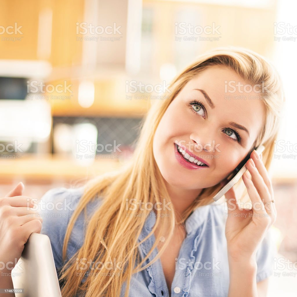 Happy woman in at home talking on smart phone royalty-free stock photo