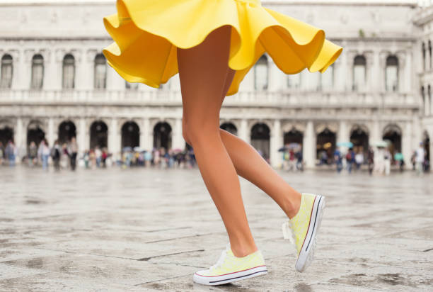 Happy woman in bright yellow skirt and sneakers stock photo