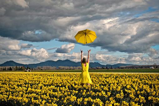 Happy woman in daffodil field with yellow umbrella