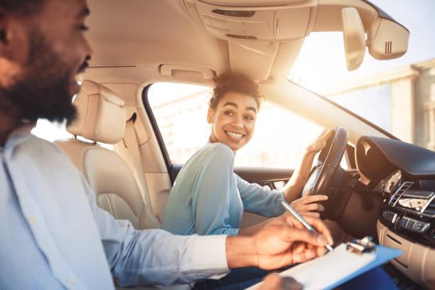 mujer feliz en el coche de examen, sonriendo a instructor masculino - aprender a conducir fotografías e imágenes de stock