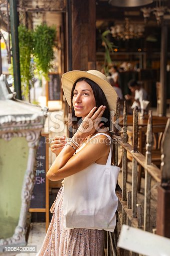 Cheerful female is travelling to tropical city and enjoying walking in streets. Tourism for pleasure concept