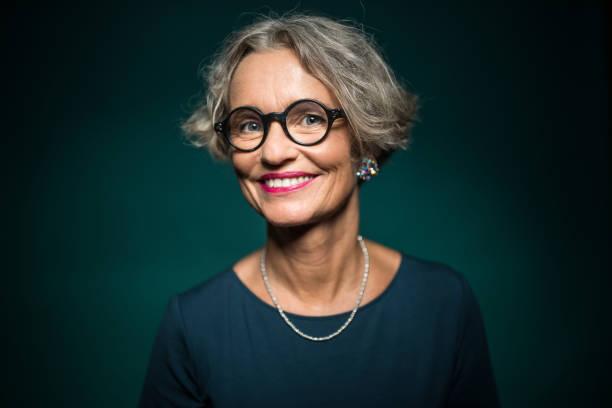 lycklig kvinna i glasögon mot grön bakgrund - mature women studio grey hair bildbanksfoton och bilder