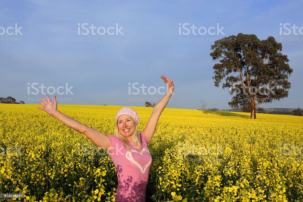 Happy woman in field of golden canola stock photo
