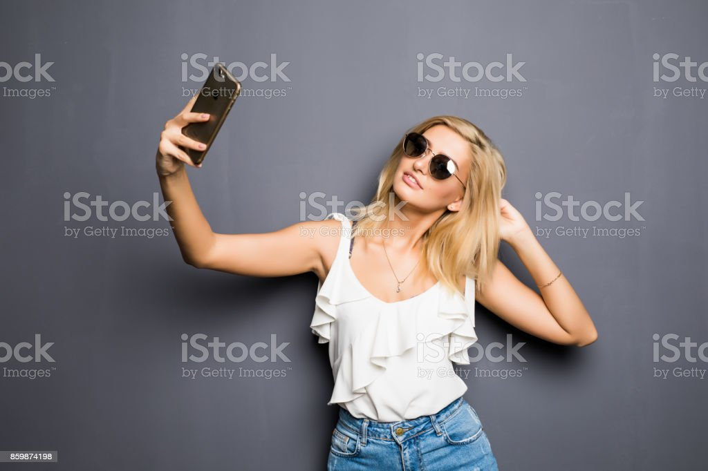 Happy woman in glasses with beaming smile making selfie on gray stock photo