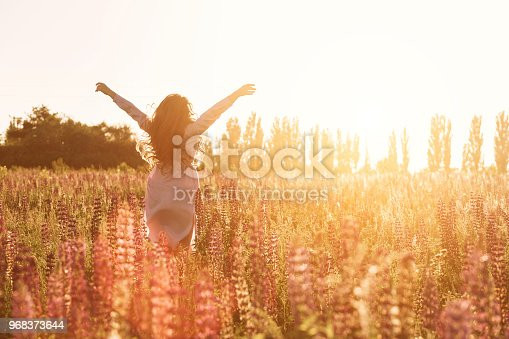 Happy woman in green flower field raised hands to sky. Warm soft sunset light.