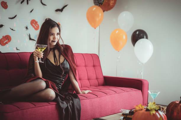 glückliche frau in halloween-kostüm und make-up feiern und halten champagner glas in halloween-nacht-party - dracula schminken stock-fotos und bilder