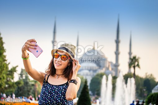Happy woman in hat and sunglasses making selfie by the smartphone on the background of the Blue Mosque, Istanbul, Travel and vacation in Turkey concept