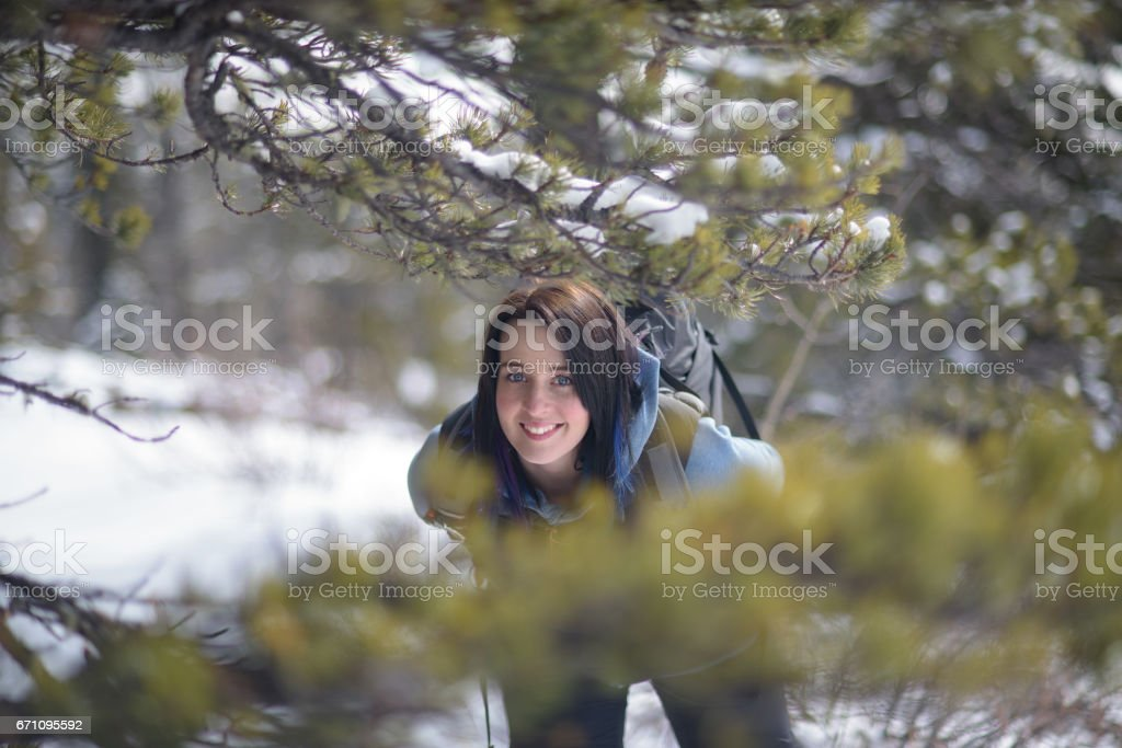 Happy woman in her 30s smiles between pine tree in the rocky mountains stock photo