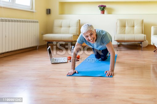 Mature woman exercising at home, looking for new exercise online on laptop.