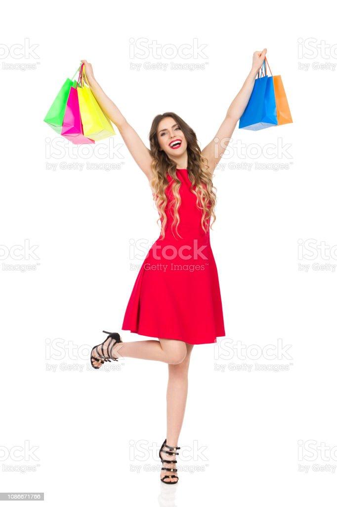 7e286f7dd06 Heureuse femme en robe rouge est debout sur une jambe et la tenue des sacs  colorés