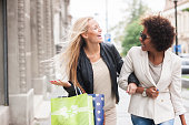 Two attractive young girls holding shopping bags while walking on the street laughing and smiling