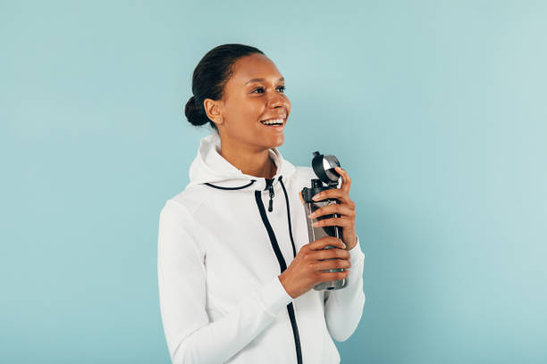Happy woman in sports clothes holds a water bottle and looking away in studio over blue background stock photo