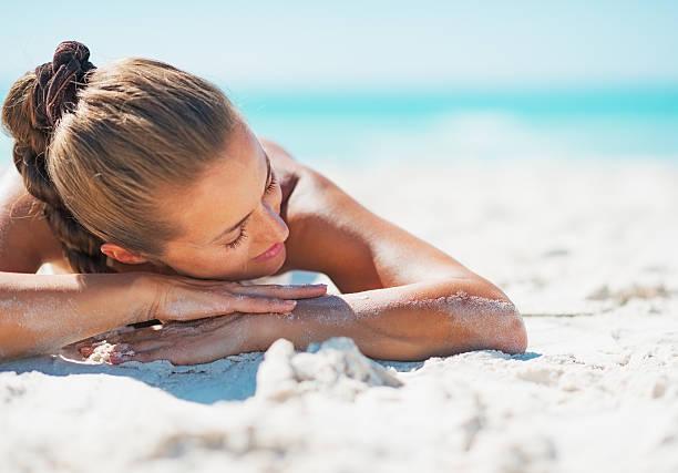felice donna in costume da bagno rilassante e sdraiati sulla spiaggia di sabbia - abbronzarsi foto e immagini stock