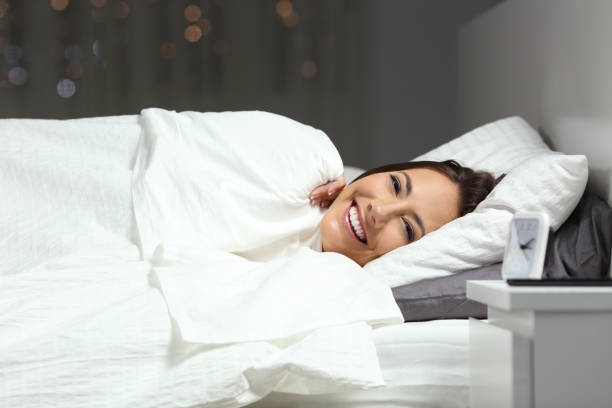 Happy woman in the bed looking at camera in the night stock photo