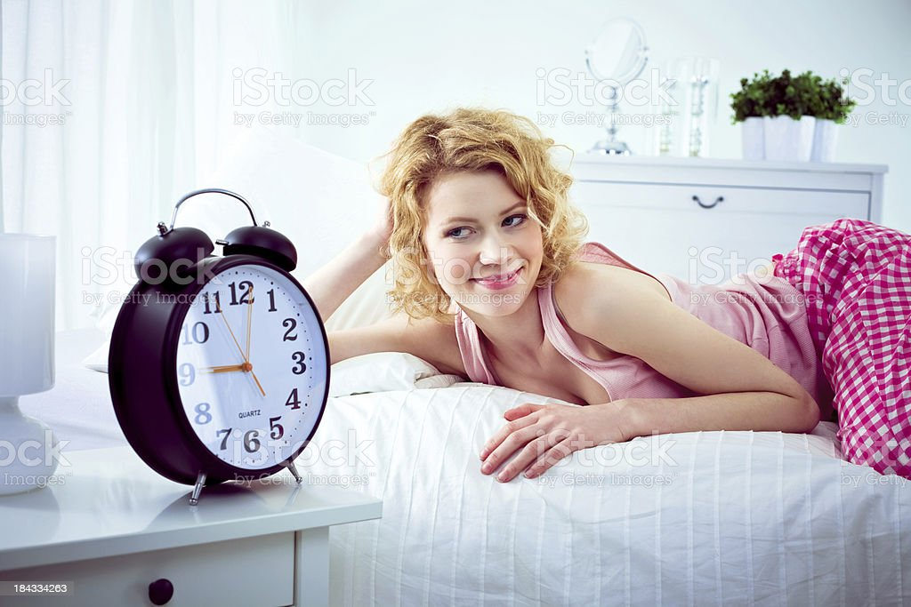 Happy woman in the morninig Happy and slept well young adult woman lying in the bed in a bedroom and looking at a big alarm clock. 25-29 Years Stock Photo