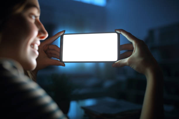 Happy woman in the night watching blank phone screen stock photo